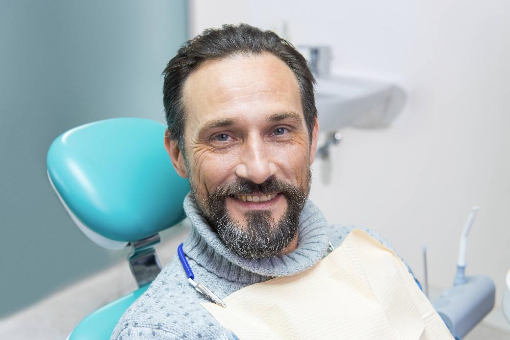 man sitting in dental exam chair smiling l new orleans dentist